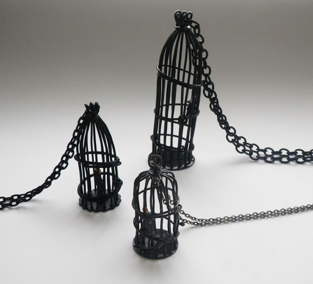 bird cages with small business men or bankers inside made of copper  and powder coated in black
