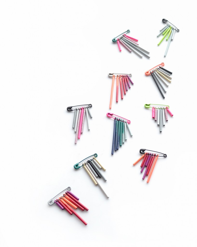 a collection of safety pin fringe brooches with an ombre powder coat